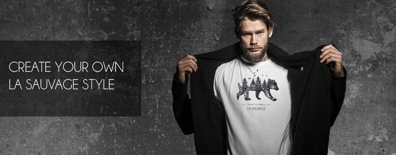 Man met blond haar en zwart vest. Toont zijn La Sauvage shirt met de afbeelding van een beer en de coördinaten van Rotterdam.