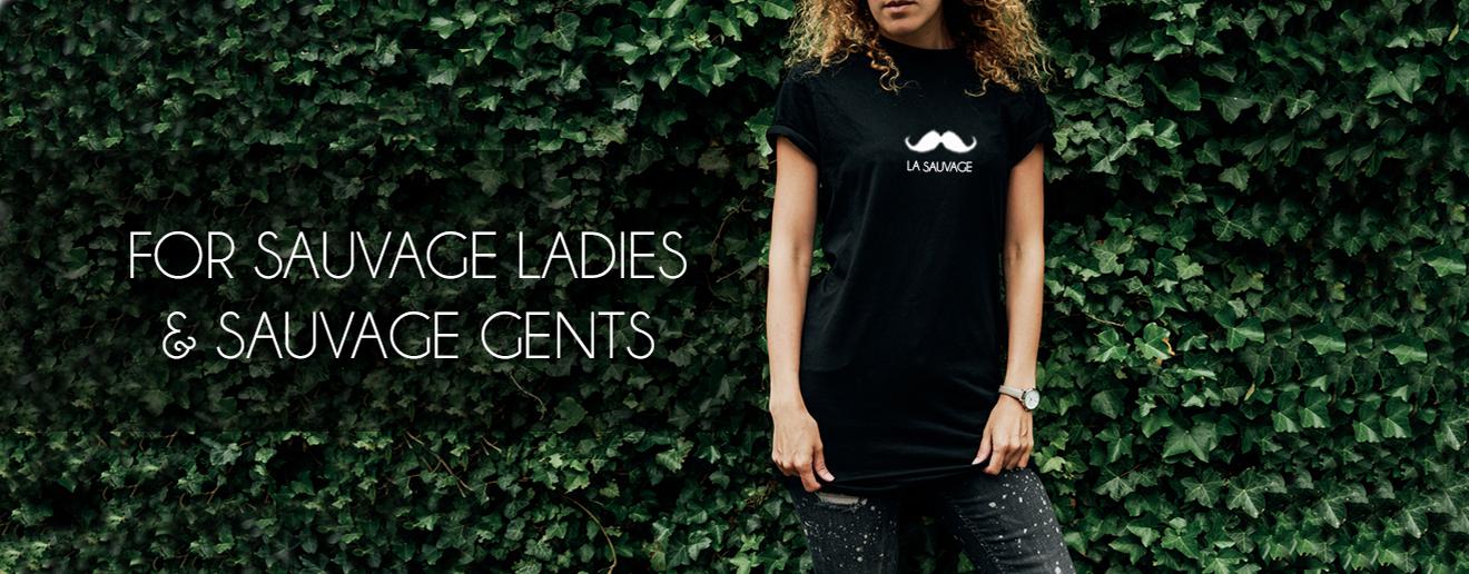 Vrouw met zwart La Sauvage t-shirt aan. La Sauvage snor met een achtergrond van klimop.