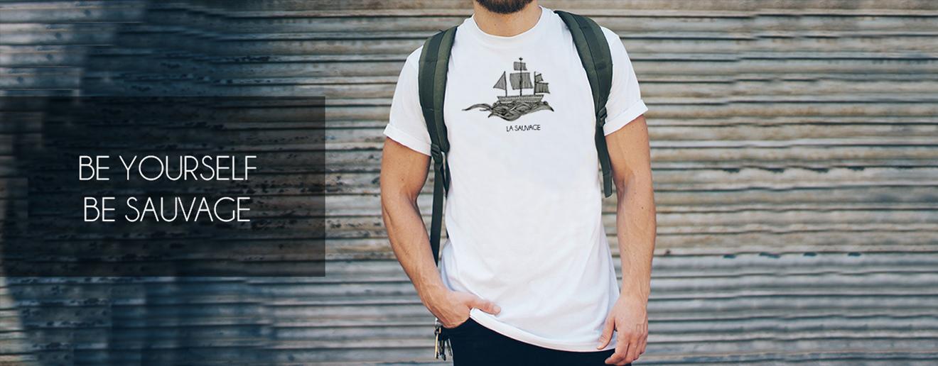 Man met wit La Sauvage shirt aan met daarop een afbeelding van een zwarte boot met grote golf. Staat voor een garage deur.