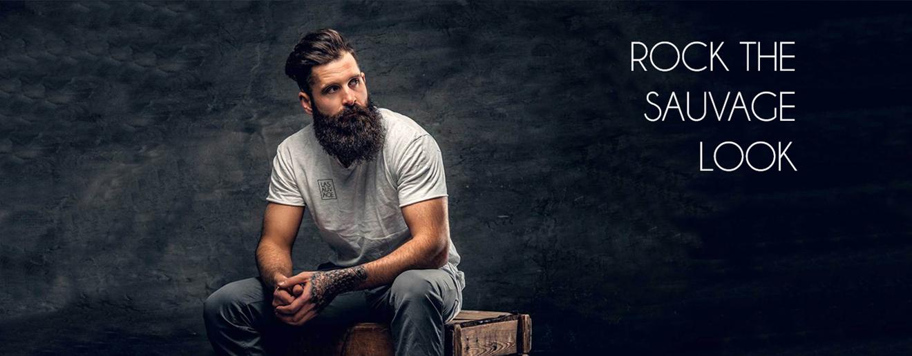 Met met donkere baard. La Sauvage shirt met subtiel logo. Donkere achtergrond.